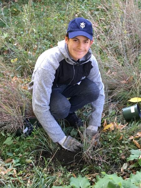Volunteer Michael Cherkasky plants grasses in Nan's Meadow